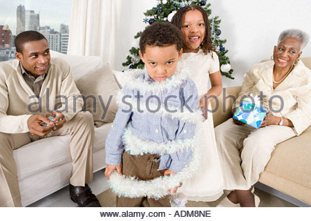 Girl wrapping brother in tinsel - Stock Photo