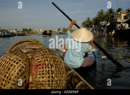 A woman paddles a boat near the central market in Hoi An Vietnam - Stock Photo