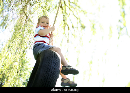 Young boy sitting on tire swing - Stock Photo