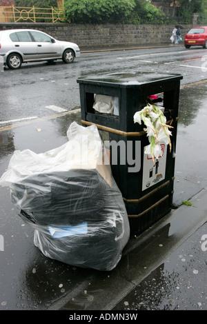litter piled up in plastic bag and overflowing public litter bin with dead flowers on wet roadside in Belfast - Stock Photo