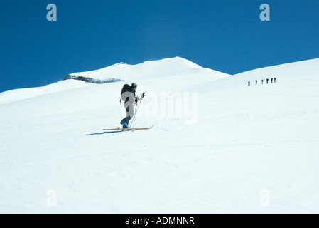 Skier looking toward group in distance - Stock Photo
