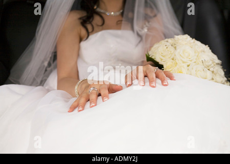 Detail shot of the bride s dress and the wedding ring on her hands - Stock Photo