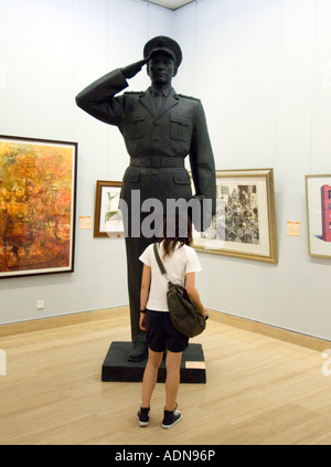 Visitor looking at large sculpture of soldier at the National Art Museum of China 2007 - Stock Photo