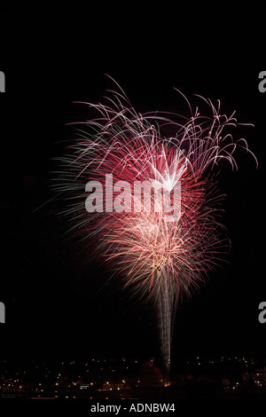 A firework display over houses in the South West of England A variety of colours forming a type of Ice cream cone - Stock Photo