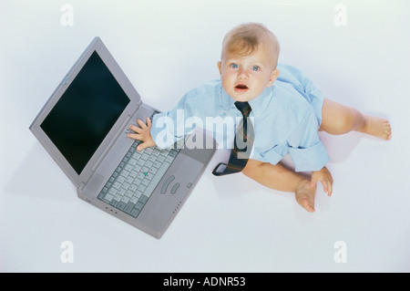 Portrait of a baby boy touching a laptop - Stock Photo