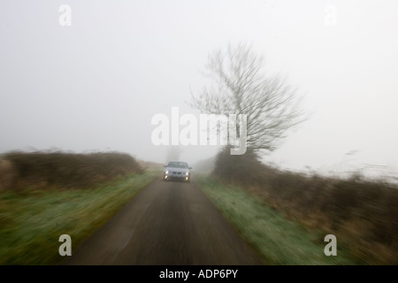 BMW 5 series car drives along empty country road in adverse foggy weather Oxfordshire England United Kingdom - Stock Photo