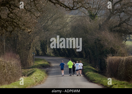 Joggers keeping fit out jogging in country lane Bourton on the Water The Cotswolds United Kingdom - Stock Photo