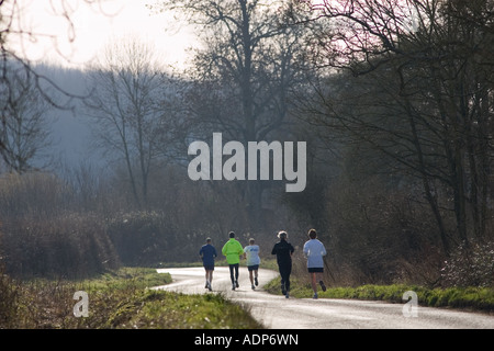 Joggers in country lane Bourton on the Water The Cotswolds United Kingdom - Stock Photo