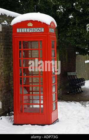 Snow covered red telephone box in Hampstead North London United Kingdom - Stock Photo