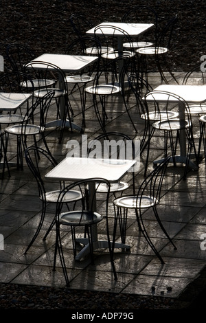 Deserted tables and chairs out of season on Brighton beach South Coast England United Kingdom - Stock Photo
