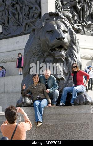 Tourists pose for photographs on lion statue at base of Nelson s Column Trafalgar Square London UK - Stock Photo