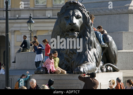 Tourists pose for photographs on lion statue at base of Nelson s Column Trafalgar Square London UK - Stock Photo