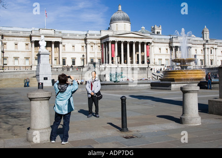 Tourists pose for photographs in front of National Gallery in Trafalgar Square London United Kingdom - Stock Photo