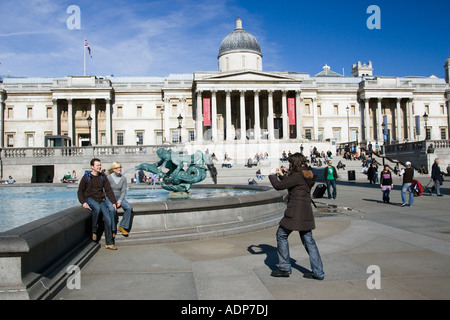 Tourists pose for photographs in Trafalgar Square by National Gallery London United Kingdom - Stock Photo