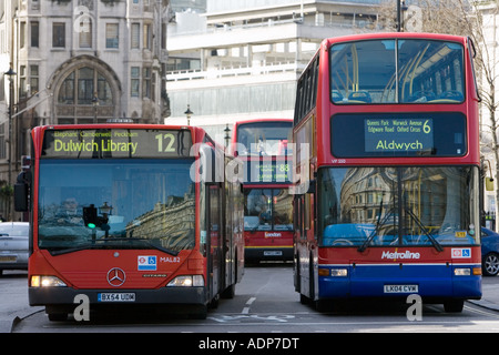 Public transport buses travel in heavy traffic in Trafalgar Square London city centre England United Kingdom - Stock Photo