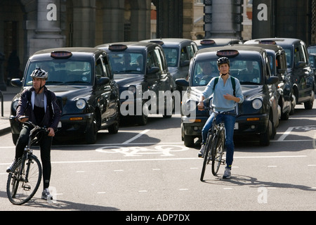 Two cyclists and black taxis in traffic waiting in Trafalgar Square downtown London city centre England United Kingdom - Stock Photo