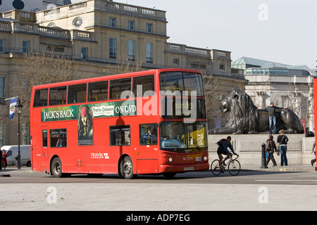 Public transport double decker bus travelling in Trafalgar Square London city centre England United Kingdom - Stock Photo