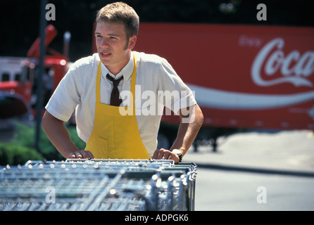 Caucasian teenage grocery clerk collecting shopping carts - Stock Photo