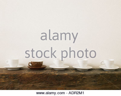 Brown cup in line of white cups - Stock Photo