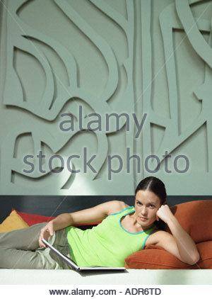 Woman reading a book on sofa - Stock Photo