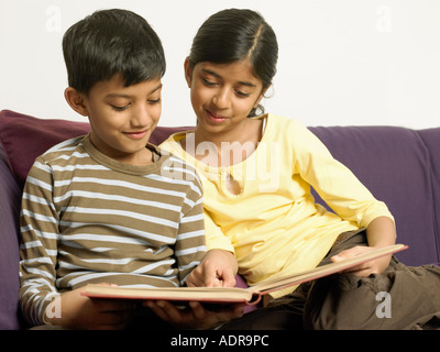 Brother and sister sitting on sofa - Stock Photo