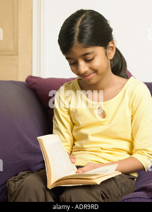 Girl reading a book on sofa - Stock Photo