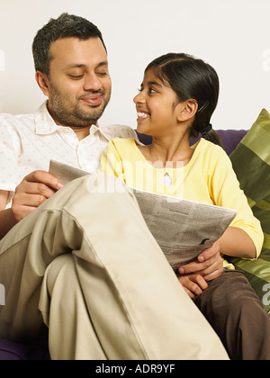 Father and daughter reading a newspaper - Stock Photo