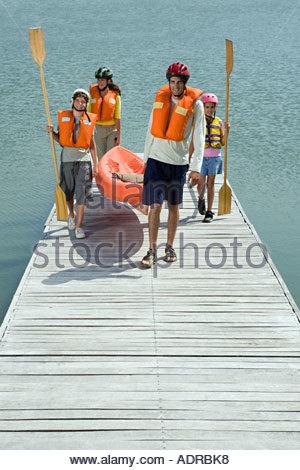 Family on jetty with canoe - Stock Photo