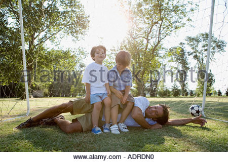 Boys sitting on top of dad - Stock Photo
