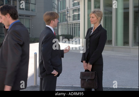 2c5c7c15fdf0 business man discusses with another · Man and woman in business clothing  converse while another businessman passes by - Stock Photo