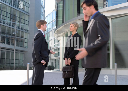 81278f06f1f9 ... Man and woman in business clothing converse while another businessman  passes by - Stock Photo