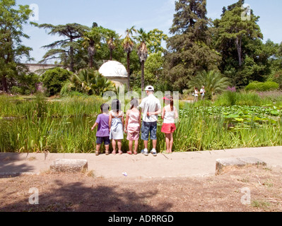 five small children stand in a line looking into a large pond - Stock Photo