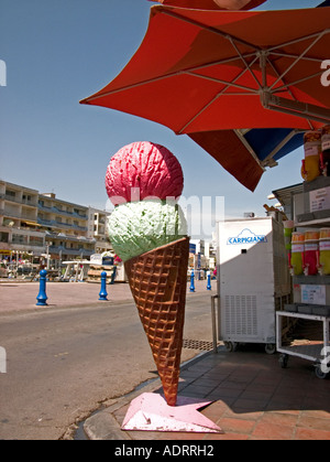 a large sculpture of an ice cream under a parasol on a pavement - Stock Photo