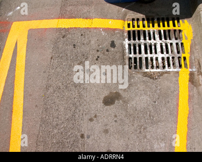 A detail of a freshly painted yellow road marking and a drain  from above