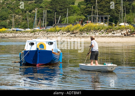 Carrick Roads at St Just in Roseland man standing in small boat and paddling out to nearby moored cabin cruiser - Stock Photo
