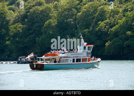 Trelissick river tour boat with passengers on Carrick Roads with woodland beyond - Stock Photo