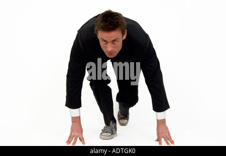 businessman on the starting blocks about to run - Stock Photo