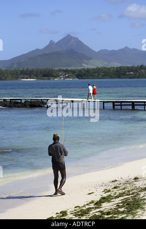 fisherman walking along sandy beach - Stock Photo