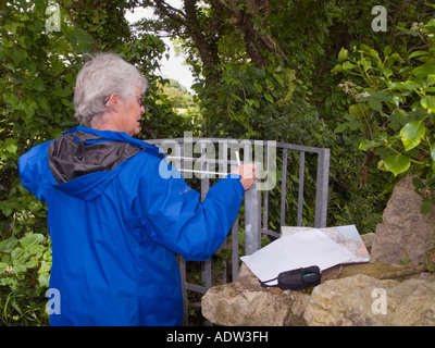 Footpath volunteer measuring narrow metal rural 'kissing gate' in stone wall on public footpath UK - Stock Photo