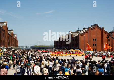 group of chinese dragon dancers in procession Akarenga red brick warehouses - Stock Photo