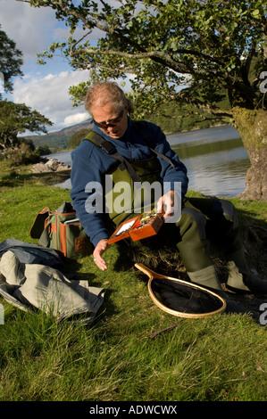 man choosing the most appropriate fly to use as bait on his line when fishing on Lake Cynwch near Dolgellau Gwynedd - Stock Photo
