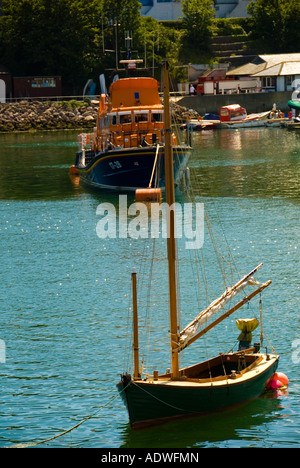 Wooden Sailing Boat Moored in Brixham with an RNLI Boat in the background - Stock Photo
