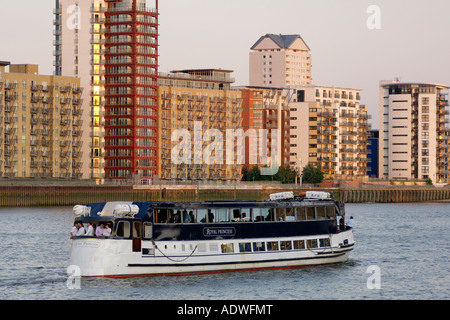 View of a Thames River pleasure boat cruising past the apartment buildings of Ocean Wharf on the Isle of Dogs in - Stock Photo
