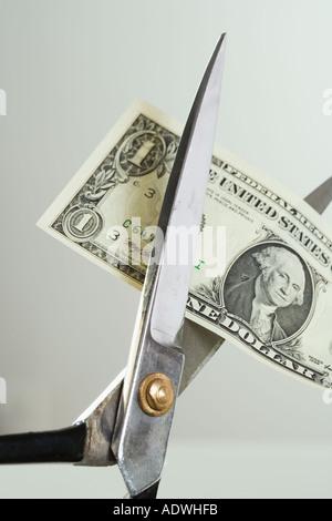 Closeup of scissors cutting money - Stock Photo