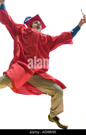 A recent graduate jumps for joy while holding his new dipolma - Stock Photo
