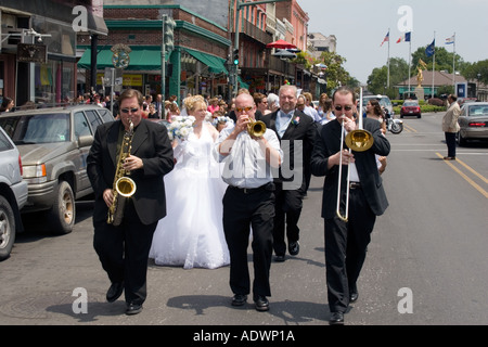 Musicians lead a wedding parade down a major street in New Orleans - Stock Photo