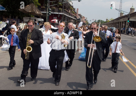 Musicians lead a wedding parade down a street in New Orleans - Stock Photo