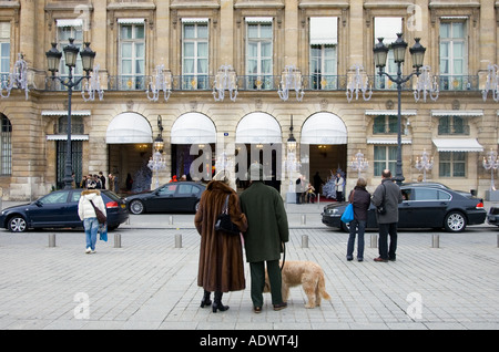 Couple with dog gaze at Ritz Hotel in Place Vendome Central Paris France - Stock Photo