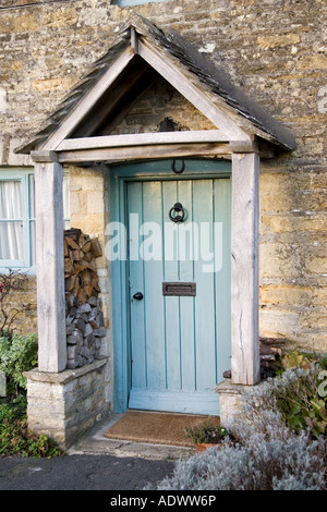 Front door and porch of typical Cotswolds cottage in village in Oxfordshire England United Kingdom - Stock Photo