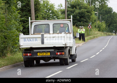 Police officers with a hand held laser speed camera detector - Stock Photo